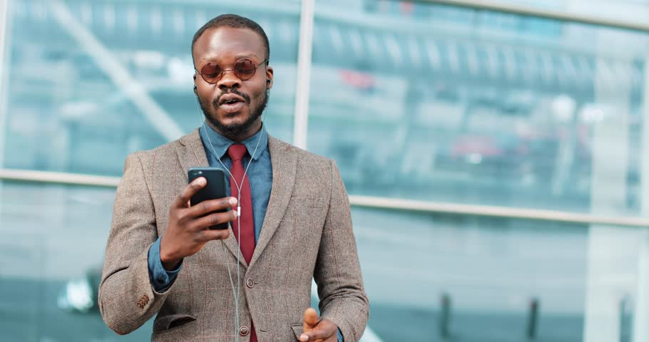 Portrait of young african american man talking using smartphone video chat technology stands next to the office center dressed in a business suit with sunglasses | Shutterstock HD Video #1011529592