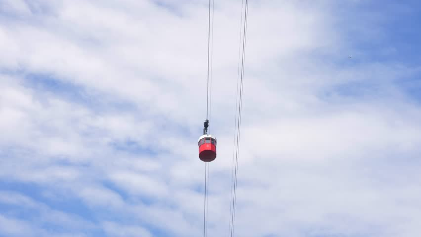 Red cable car passing from bottom to top of the frame with blue sky in the background