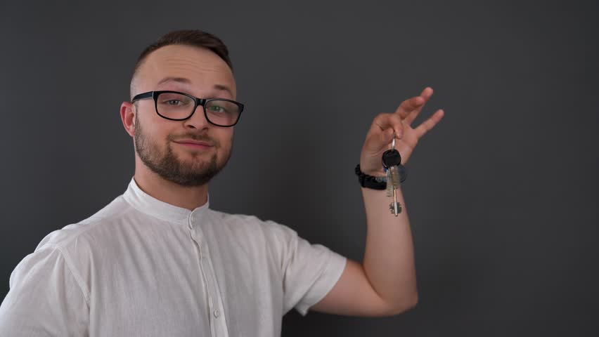 A young, bearded man with glasses. Studio shot of male hold keys in his hand. Smiling and shaking keys. | Shutterstock HD Video #1011536936