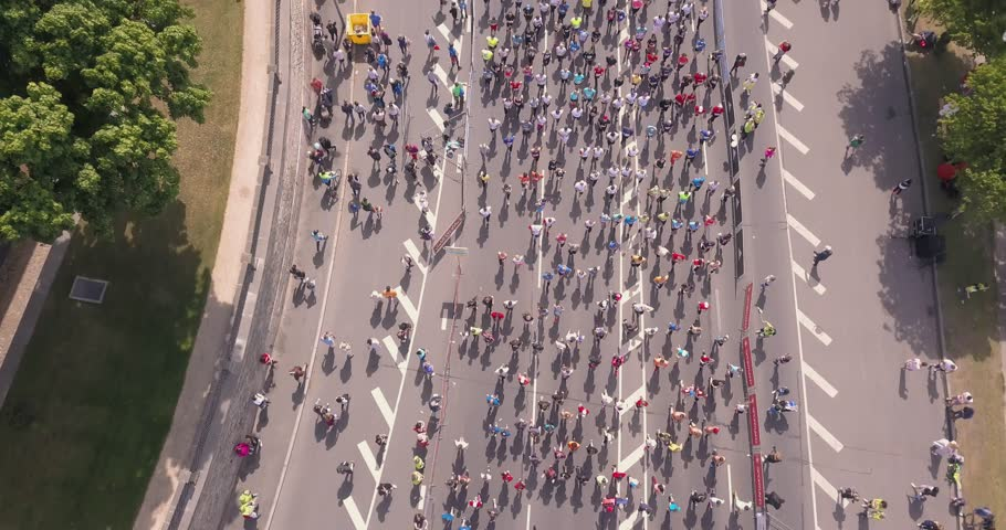 Aerial view from drone on crowd of people who is starting their run on marathon event. Funny shadows on asphalt. | Shutterstock HD Video #1011544178