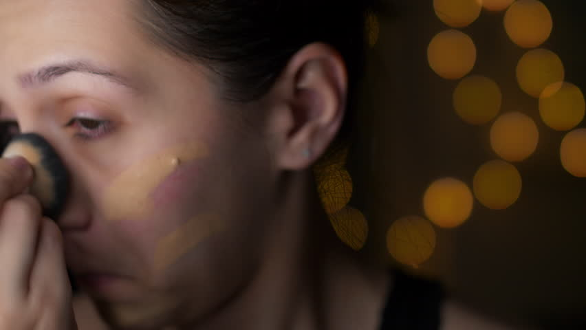 Female Applying Foundation Makeup Close Up. a slow motion closeup view of a womans face applying foundation makeup with a brush #1011547214