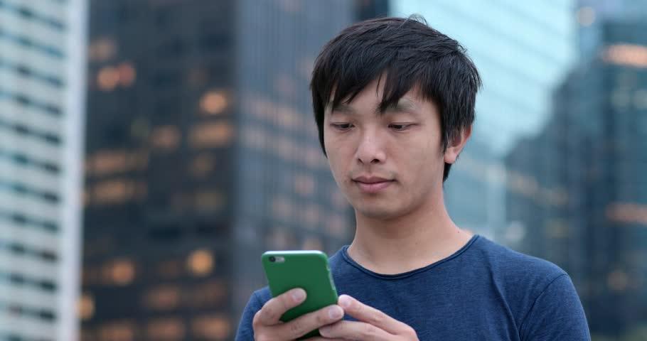 Man look at smart phone at outdoor park #1011548189