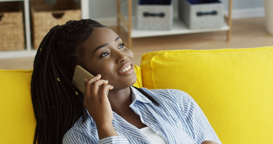 Portrait of the young pretty African American woman talking cheerfully on the phone while sitting on the yellow soda at home. Indoors | Shutterstock HD Video #1011553220