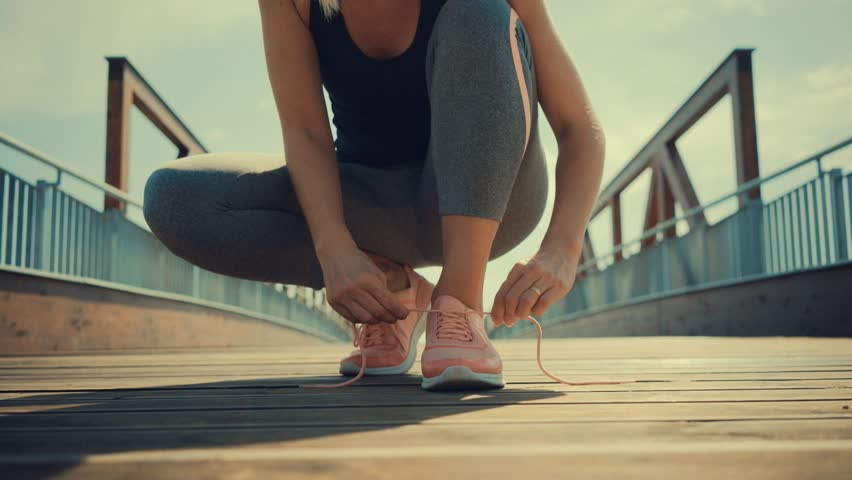 Running woman. Girl run and jogging training close-up sneakers in bridge background in sunny day #1011557093
