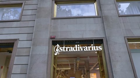 Barcelona, Spain - May 16, 2018: Tilt down shot of a Stradivarius store front with people passing by. Stradivarius is an international women and men clothing fashion brand from Spain.