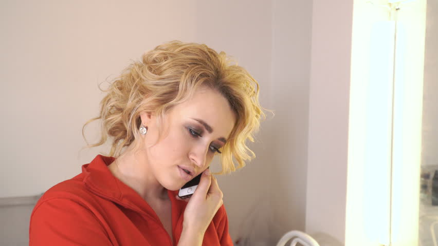 20s girl is talking on the phone smiling and laughing. Blonde put the phone to her ear and talks cheerfully. Happy talking on cell phone. Woman is sitting in a red sweater in an elephant at stylist. | Shutterstock HD Video #1011579704