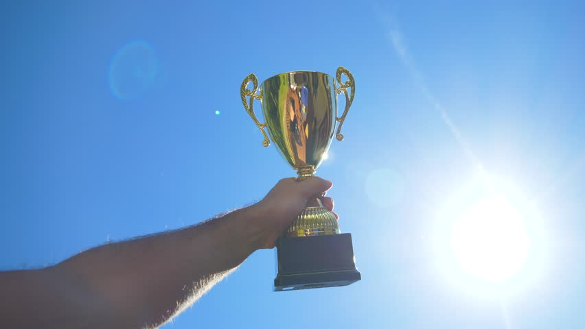 Golden trophy prize is lifted up in the air, Wide.