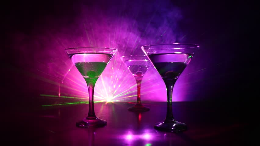 Several glasses of famous cocktail Martini, shot at a bar with dark toned foggy background and disco lights. Club drink concept. Selective focus. Slider shot