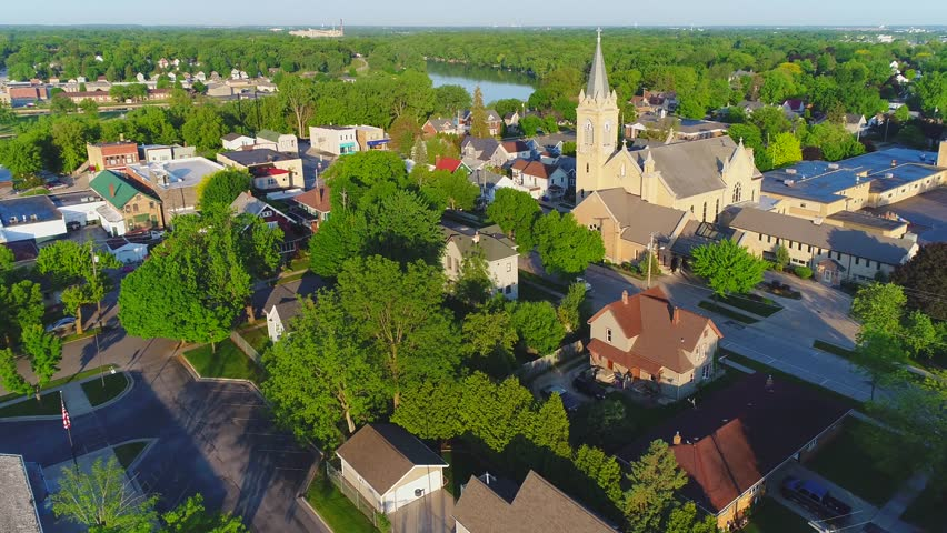 Small town America, scenic sunrise flyby of church steeple.