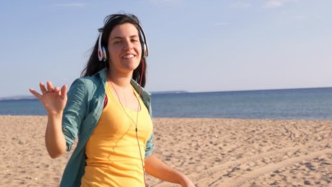 Young brunette woman standing at the beach right next to the sea, listening to music with headphones on, dancing with her eyes closed