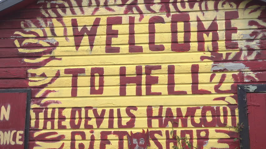 HELL, GRAND CAYMAN/CAYMAN ISLANDS - JANUARY 20, 2018: Welcome to Hell sign on gift shop, Caribbean, tilt down. Hell refers to an open space filled with clusters of short black limestone.   Shutterstock HD Video #1011611189