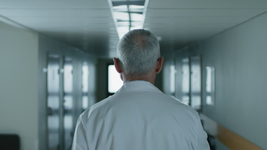 Following Shot of the Professional Male Doctor Walking Through Hospital Hallway. Portrait Footage. Shot on RED EPIC-W 8K Helium Cinema Camera.