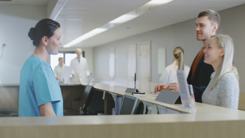 In the Hospital at the Reception Desk Nurse on Duty Talks With Patients and then Picks up the Phone to answer Emergency Call. Shot on RED EPIC-W 8K Helium Cinema Camera. | Shutterstock HD Video #1011621821