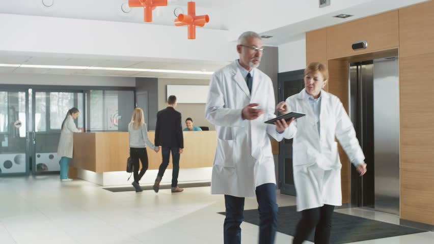 In the Hospital Young Couple Walks to Reception. Medical Personnel, Doctors, Nurses, Assistants and Patients in the Busy Lobby. New, Modern Medical Facility. Shot on RED EPIC-W 8K Helium Cinema Camera