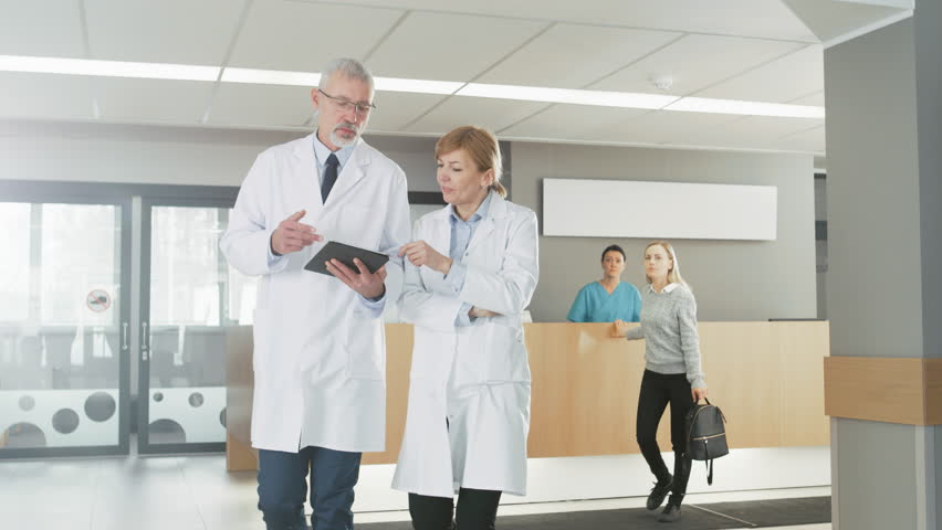 In the Hospital, Busy Doctors Talk, Using Tablet Computer While Walking Through the Building. In the Background Patient Talks with Receptionist. New Modern Fully Functional Medical Facility. 4K UHD.