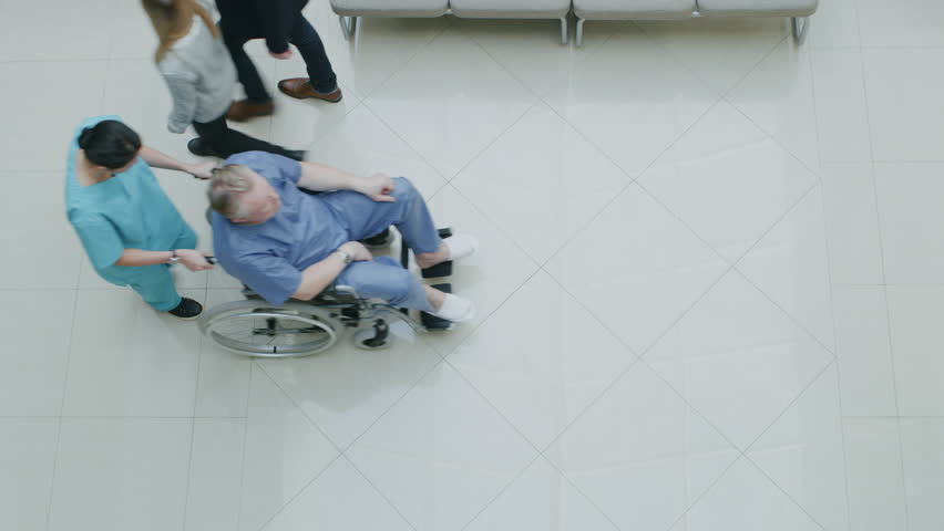 High Angle Shot In the Hospital Lobby of Medical Personnel Pushing Patients in Wheelchairs, Doctors and Patients Working and Walking. New, Clean Hospital. Shot on RED EPIC-W 8K Helium Cinema Camera.