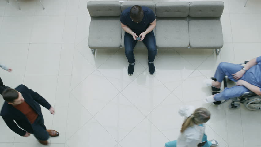 High Angle Shot in the Hospital Lobby, Young Man Waits for Results while Sitting and Using Mobile Phone, Doctors, Nurses and Patients Walk Past Him. Clean, New Hospital. Shot on RED EPIC-W 8K Camera.