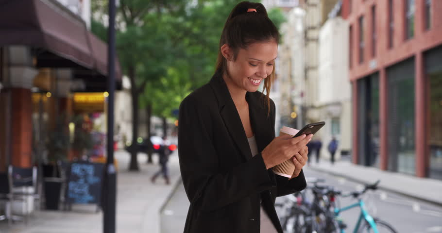 Young Caucasian business woman text messaging outside cafe on mobile phone while downtown. Happy Millennial Professional female texting with smartphone in the city by coffee shop. 4k | Shutterstock HD Video #1011645164