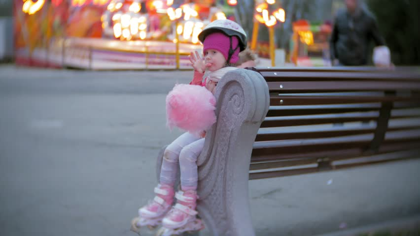 Beautiful little girl sitting on a bench in an amusement park, eating pink sweet cotton candy rolling on roller skates 4k