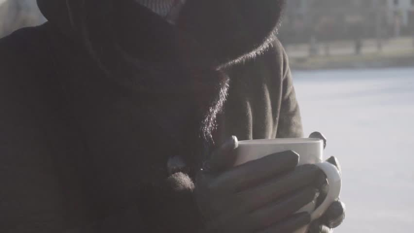 Girl`s hands holding Cup of hot tea or Coffee in park. close up
