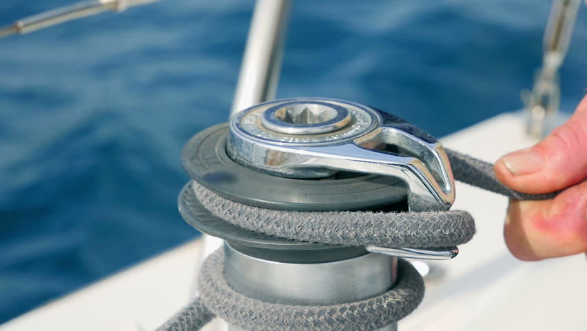 Sailor mans hand winding up grey rope arround sailing boats side winch. Closeup on sailor securing rope. Filmed on sailing tip in Adriatic sea in slow motion hd.