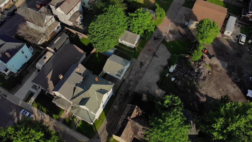 A slow reverse aerial establishing shot of a residential neighborhood in a Pennsylvania small town. Tilt up to reveal the business district and Ohio River in the distance. Pittsburgh suburbs.