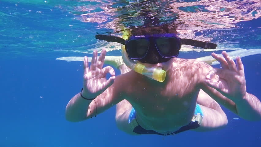Boy dive in Red sea near coral reef, showing ok symbol, underwater shoot