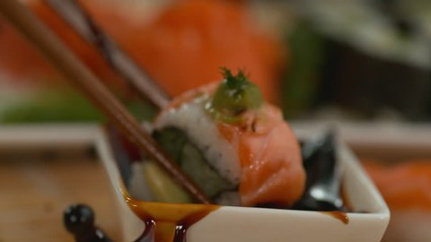 Closeup dipping sushi into soy sauce in super slow motion