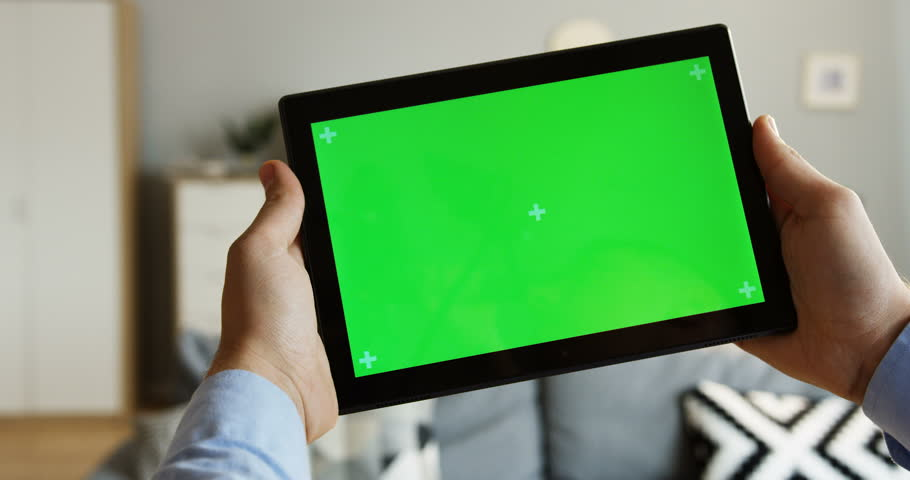 Close up of the male hands holding a black tablet computer horizontally with a green screen and tracking motion. At home. Chroma key. Inside | Shutterstock HD Video #1011686669