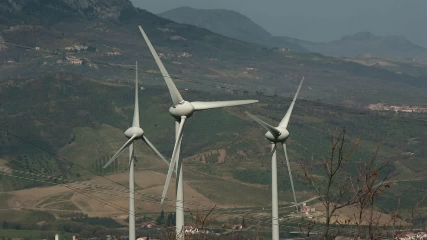 Group of blades of a wind power plant moving under a light wind. The wind farm located on a windy pass between two mountain valleys.  #1011700319
