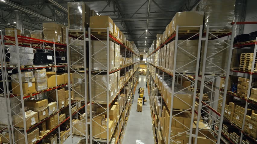 Boxes stored on high shelves at industrial warehouse. Finished goods in trading warehouse on production plant drone view | Shutterstock HD Video #1011706778