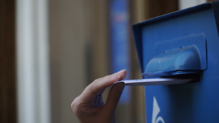 Woman is Sending a paper Letter into a blue Letterbox. The girl throws a white letter in the Mailbox. Greeting card. 4K. Invitation card UItraHD. Love letter.     Shutterstock HD Video #1011717254