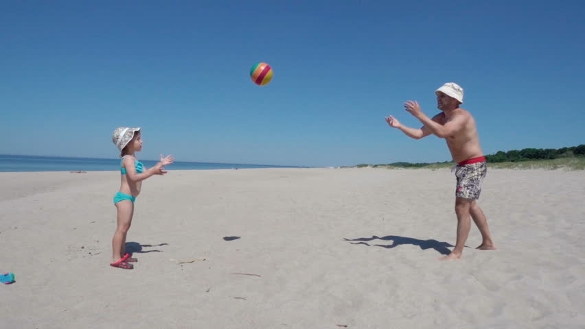American father enjoying playing ball with young little kid on beach. Family Summer Beach Vacation. Slow Motion.