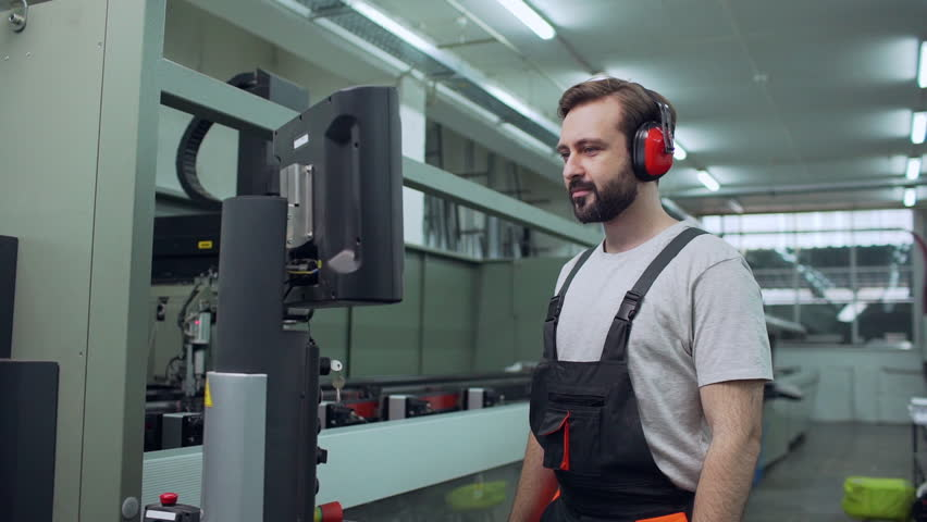 Portrait of adult employee man 30s wearing working overall and headphones touching with equipment and starting mechanism in large facility, slow motion #1011732215