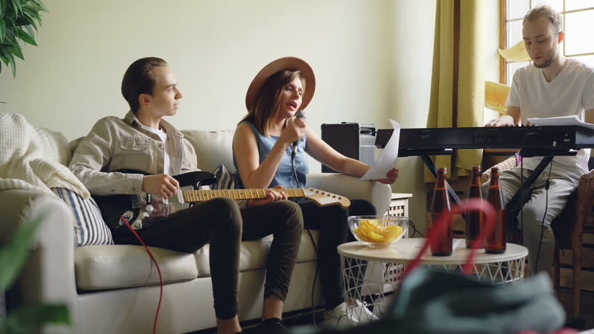 Young people popular band are holding rehearsal at home, singing and playing the keyboard and the guitar and checking paper with lyrics and music sheet.