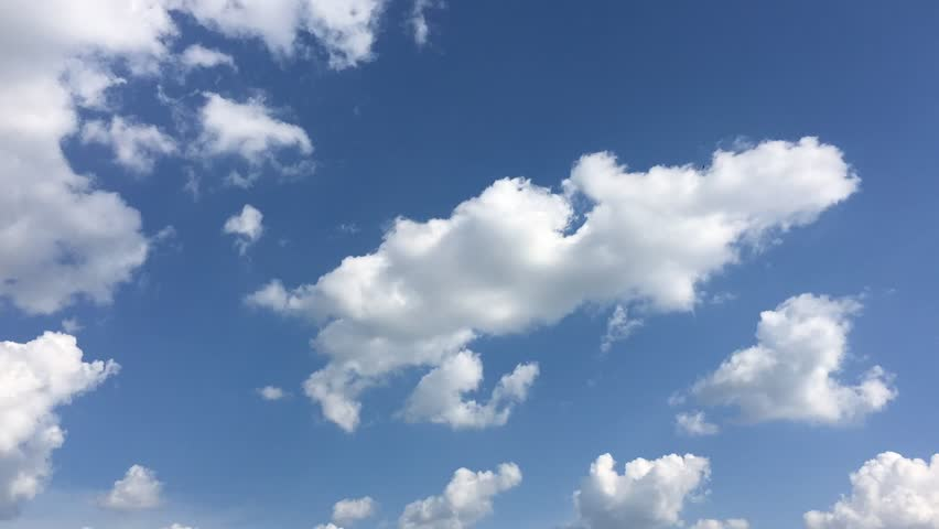 White cloud disappear in the hot sun on blue sky. Cumulus clouds form against a brilliant blue sky. Time-lapse motion clouds blue sky background.