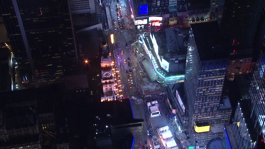 Top down view aerial night time establishing shot straight down of busy traffic on New York City manhattan street through tall buildings into Times Square. NX HD stock video