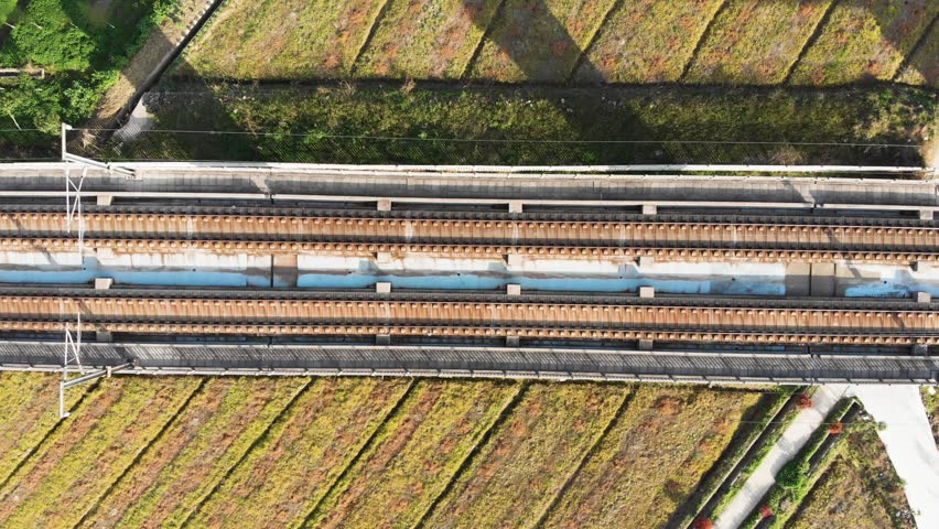 Looking down at Chinese high speed train tracks on raised platform. Drone shot of moving gaotie on elevated railway.