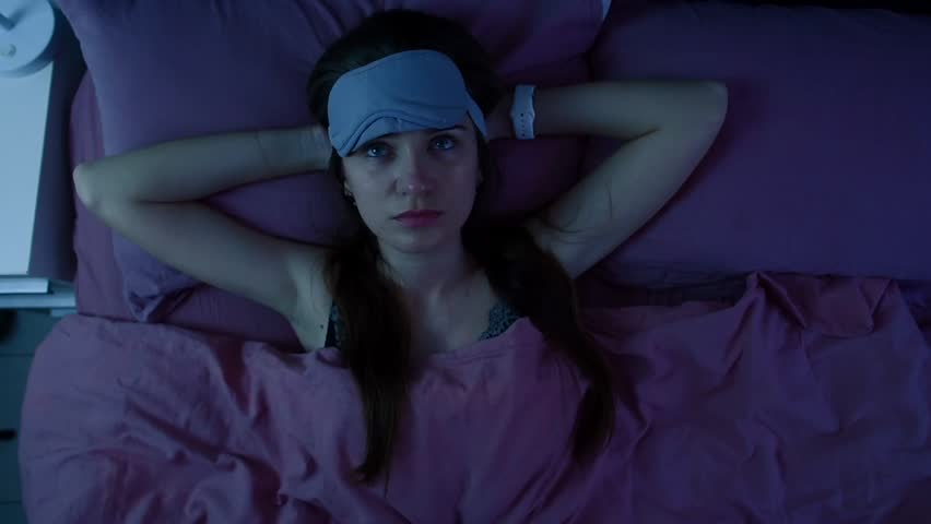 Young attractive awake girl can't sleep because of insomnia. Apatic woman disturbed by the noise made by neighbours is staring at the ceiling. Top view. | Shutterstock HD Video #1011765779