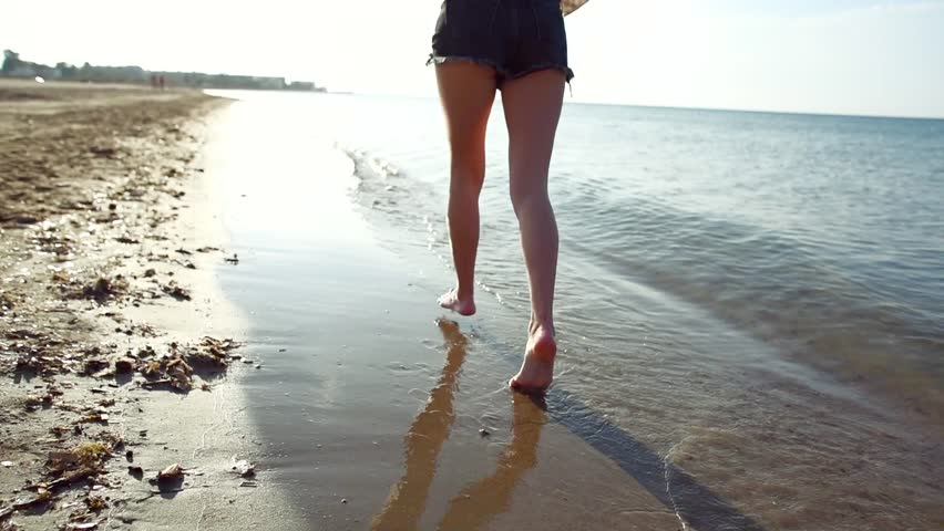 Slow motion of young female legs walking and splashing in the sea on sunny summer day. Tourism, travel and vacations concept. | Shutterstock HD Video #1011765791