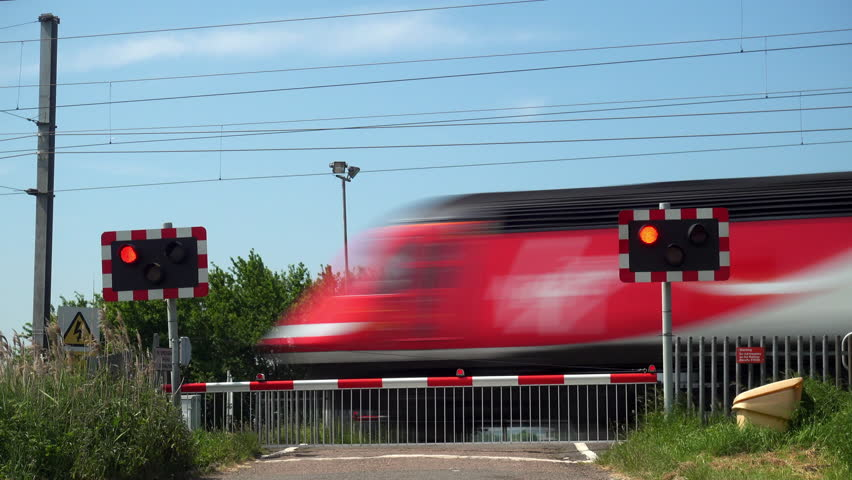 Cambridgeshire, UK - May 23, 2018: A Virgin Trains High Speed Train HST 125  passenger train heading south and a class 91 electric passenger train heading north pass over a roadway level crossing.