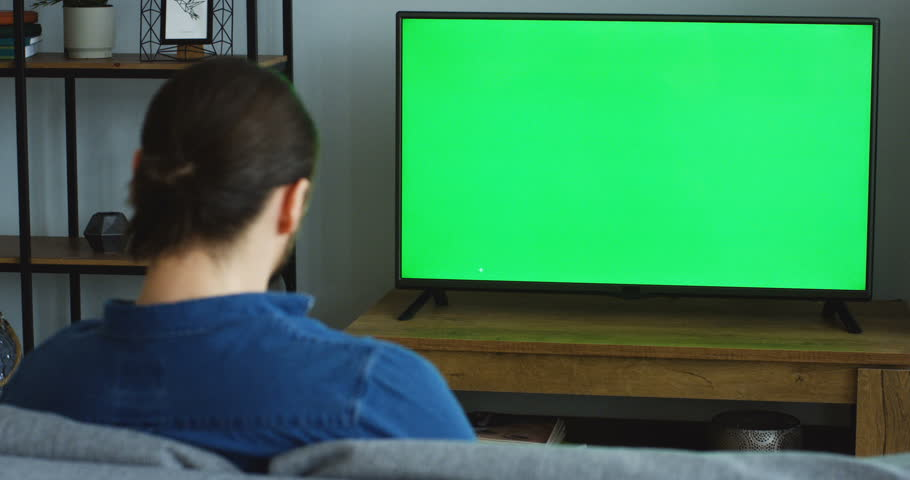 Rear of the man in the jeans blue shirt sitting on the sofa in the living room and watching TV with green screen. Chroma key. Indoor | Shutterstock HD Video #1011778658