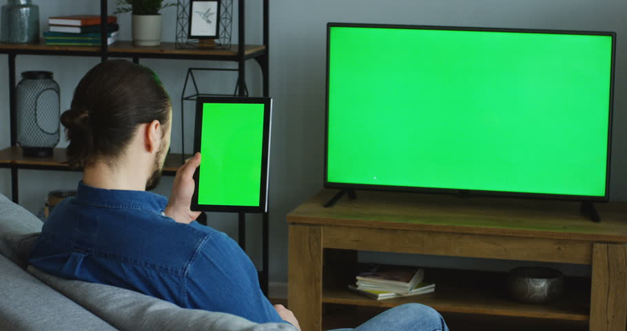 View over the shoulder on the Caucasian man watching TV with green screen while sitting on the sofa in the living room and scrolling on the black tablet computer with green screen in focus vertically | Shutterstock HD Video #1011778664