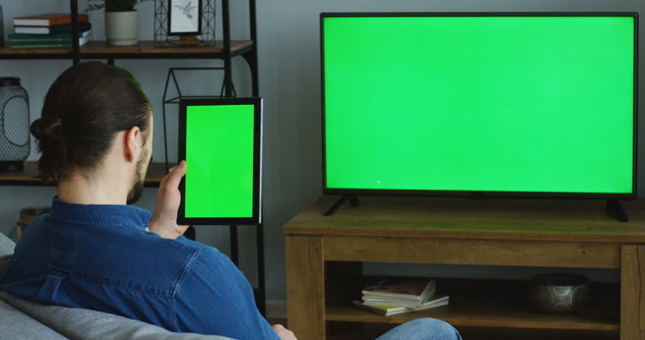 Rear view on the young man sitting at home, watching TV with green screen and scrolling on the black tablet device with green screen vertically. Tablet in focus. Chroma key. Inside | Shutterstock HD Video #1011778676