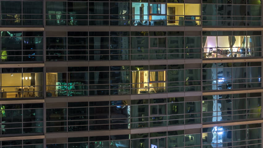 Glowing windows of skyscrapers at evening timelapse. View of modern residential and office high-rise buildings in Dubai marina. People moving inside. Aerial top view. | Shutterstock HD Video #1011785375