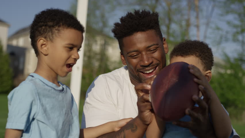 Ottawa, Canada - May 2018 - An african american father plays with his kids in a soccer pitch beside an urban housing development setting a positive example for the next generation of children   Shutterstock HD Video #1011786824