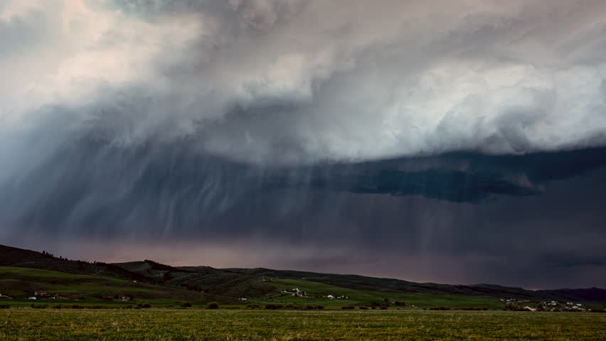 Storm clouds rolling in the sky during rain storm in time lapse as it moves across the landscape and lightning strikes during severe storm in wyoming.
