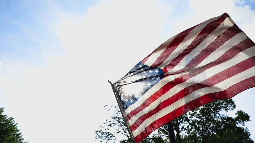 American flag in neighborhood flies in wind from low angle slow motion right justified