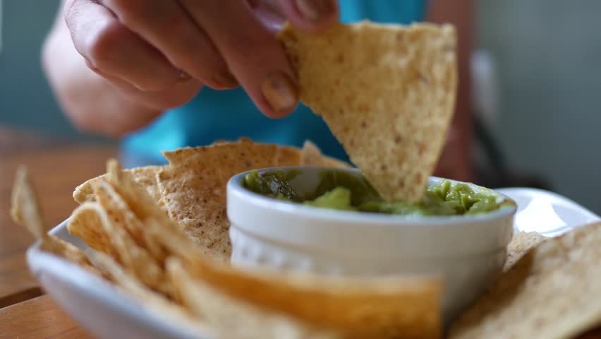 Person eating guacamole while scooping a chip Royalty-Free Stock Footage #1011792728