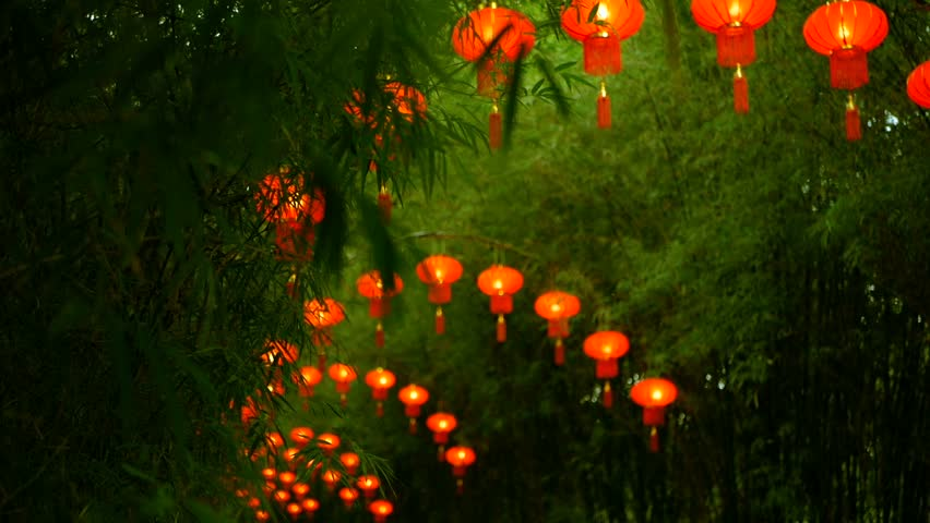 Rows of traditional chinese style red lanterns hanging on bamboo tree tunnel arch. Decoration lamps for Chinese Lunar New Year festival.